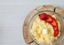 Gruau de maïs avec des fraises - le petit déjeuner a servi sur le bois scié naturel Images stock