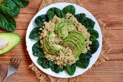 Gruau de quinoa avec les épinards et l'avocat Salade savoureuse d'avocat d'épinards de quinoa d'un plat blanc Fond en bois de Bro Images stock