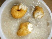 Gruau de riz avec le bâton frit de la pâte dans une cuvette de papier Photo libre de droits