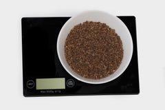 Gruau de sarrasin sur une échelle blanche numérique de cuisine (pesage pro images libres de droits