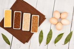 gruaux dans des cuvettes, oeufs, feuille de laurier, table-serviette sur la table en bois blanche Image libre de droits