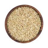 Gruaux de riz brun dans la cuvette en bois d'isolement sur le fond blanc Vue supérieure photo libre de droits