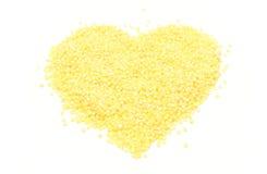 Gruaux en forme de coeur de millet sur le fond blanc Image libre de droits