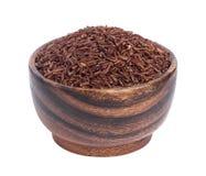 Gruaux rouges de riz dans la cuvette en bois d'isolement sur le fond blanc Photo stock