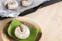 Grub Worms or Coconut Rhinoceros Beetle. Food Insects for eating larvae fried or baked on plate and on baking tray is good source. Of meal high protein edible stock photos
