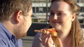 Gruba chłopaka i dziewczyny łasowania pizzy outdoors romantyczna data, szybkie żarcie dieta zdjęcia stock