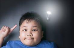Gruba chłopiec dostaje genialnego pomysł pod jaskrawą żarówki lampą Obraz Stock