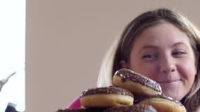 Gruba dziewczyna no może opierać się cukierki i no łama daleko od diety, stos donuts na talerza zakończeniu up zbiory
