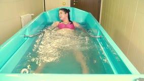 Gruba kobieta w kostiumu kąpielowym kłama w łazience z bąblami i cieszy się hydromassage, zwolnione tempo zbiory wideo