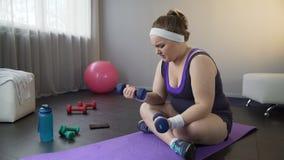 Grubej dziewczyny podnośni dumbbells siła zbroją mięśnie, robi trudnym ćwiczeniom zbiory
