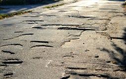 Gruben auf den Straßen des Asphalts stockbilder