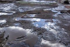 Gruben und Pfützen auf der schrecklichen Straße im Frühjahr bedeckt mit alten Teppichen lizenzfreies stockbild