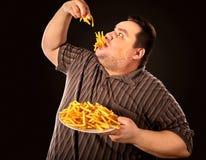 Gruby mężczyzna łasowania fasta food francuz smaży dla z nadwagą osoby Zdjęcie Royalty Free