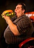 Gruby mężczyzna łasowania fasta food hamberger Śniadanie dla z nadwagą osoby Zdjęcia Royalty Free