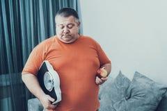 Gruby mężczyzna ja koszulka z Weighter i Apple w rękach obrazy royalty free