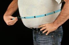 Gruby mężczyzna mierzy jego brzucha zdjęcie royalty free