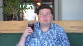 Gruby mężczyzna trzyma szkło napój koli obsiadanie w kawiarni i żuć jedzenie napój zbiory wideo