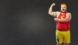 Gruby mężczyzna w sportach odziewa miary jego ręka z centim obraz royalty free