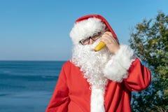 Gruby mężczyzna w szkłach ubierających jako Santa trzyma banana na oceanie Urlopowy i zdrowy styl życia zdjęcia royalty free