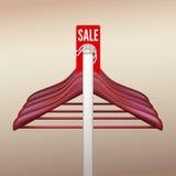 Grucce per vestiti con una vendita del segno Immagine Stock