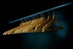Grucce per vestiti di legno vuote su una ferrovia del guardaroba immagine stock libera da diritti