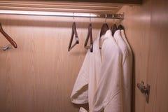 Grucce per vestiti ed accappatoio bianco fotografia stock libera da diritti