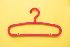 Gruccia per vestiti di plastica rossa con fondo giallo Immagini Stock