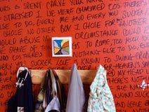 Gruccia per vestiti e scrittura sulla parete Immagini Stock