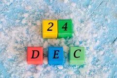 Grudnia 24 znak na kolorów drewnianych sześcianach z śniegiem Fotografia Royalty Free