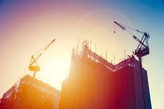 Grue avec le bâtiment en construction avec le ciel de coucher du soleil Photographie stock