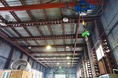 Grue avec le pont roulant et échelles dans l'entrepôt photographie stock libre de droits