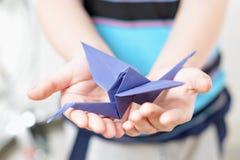 Grue d'origami chez les mains des enfants Photos libres de droits