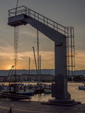 Grue dans la marina au coucher du soleil Image libre de droits
