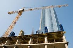 Grue de bâtiment et bâtiment en construction contre le ciel bleu Images stock