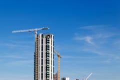 Grue de bâtiment et chantier de construction sous le ciel bleu Photographie stock libre de droits