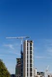 Grue de bâtiment et chantier de construction sous le ciel bleu Images stock