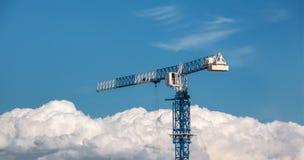 Grue de construction bleue et blanche au-dessus des nuages sur le fond de ciel bleu Photo libre de droits