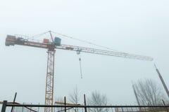 Grue de construction dans le début de la matinée de brouillard - vue urbaine image stock