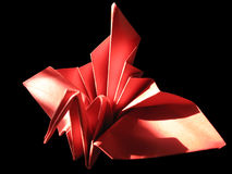 Grue de fête rouge d'Origami d'isolement sur le noir Photos stock