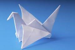 Grue de papier d'origami sur le bleu Image stock