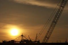 Grue de plate-forme pétrolière sur le coucher du soleil Images stock