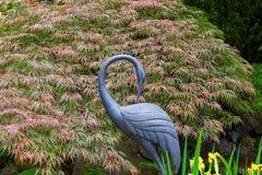 Grue en bronze avec le fond rouge d'arbre d'érable japonais photos stock