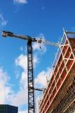 Grue fonctionnant à un bâtiment non fini avec un ciel bleu lumineux images libres de droits
