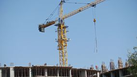 Grue fonctionnante au chantier de construction - bâtiment vivant moderne - travailleurs banque de vidéos
