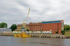 Grue jaune devant de vieux bâtiments industriels dans le port de Liepaja, Lettonie Images libres de droits
