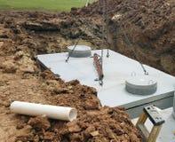 Grue mettant les réservoirs de stockage septiques dans la terre Photos libres de droits