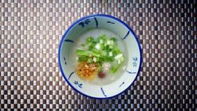 Gruel ρυζιού ή το βρασμένο ρύζι στο ύφος παράδοσης της Ταϊλάνδης στο υπόβαθρο χαλιών και έχει κάποιο διάστημα για γράφει τη διατύ Στοκ Εικόνες