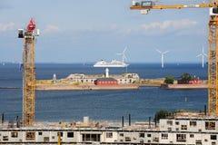 Grues à construction et à tour dans la perspective de la forteresse de Trekroner, des turbines de vent et du revêtement Photos stock