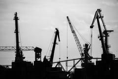 Grues de bateau-levage de cargaison sur la rivière dans la photo noire et blanche de port image libre de droits