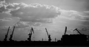Grues de bateau-levage de cargaison sur la rivière dans la photo noire et blanche de port images libres de droits